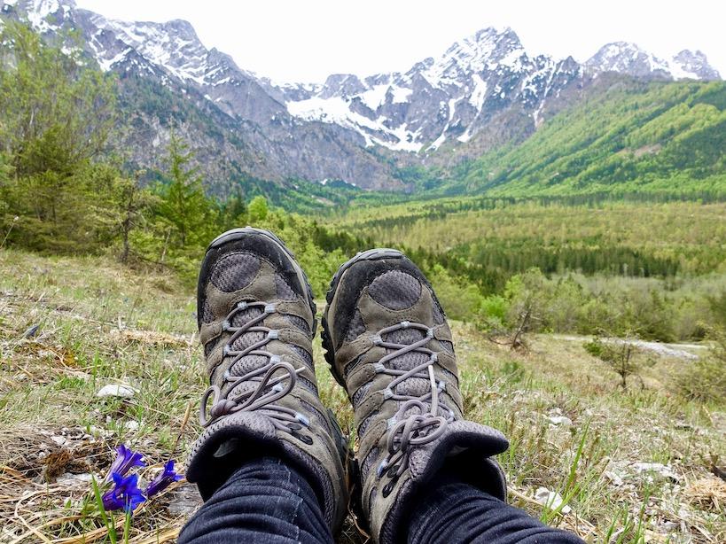 Die Füße eines Menschens, der am Wiesenboden liegt mit Bergpanorama im Hintergrund