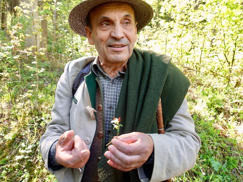 Fritz Wolf beim Erklären mit Hut und Blume in der Hand